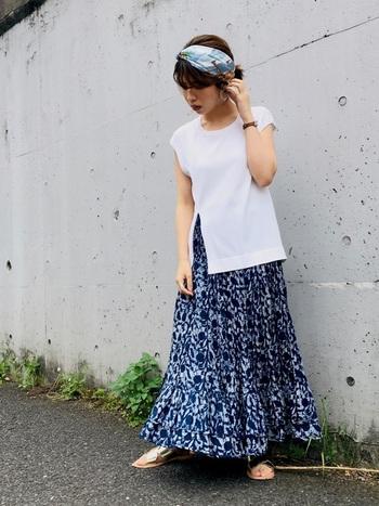 裾部分にティアードが入って、ふわりと広がるAラインが女性的なコーデです。ベーシックなフレンチスリーブトップスは、片側にスリットが入っていて、ハイウエストで着るスカートがちらりと見えますね。白×ブルーは柄物スカートでも定番の組み合わせです。