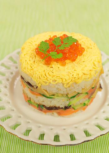 とってもきれいなミルフィーユちらし寿司は、丸い型さえあれば意外と簡単。錦糸卵を一番下に敷いたら、あとは酢飯と具材を交互に詰めていくだけ。最後にイクラとセルフィーユを飾れば、ケーキのようなデコレーションが完成します♪