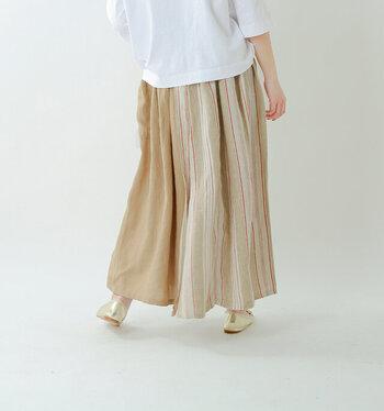 無地の麻布とストライプの麻布が重なり巻きスカートのように見える「tumugu(ツムグ)」のロングスカート。ウエストはゴム製でラクラク。アクセントとなる大きなポケットが付いています。