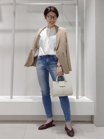 胸元にギャザーを施した甘めな白ブラウスを、ブルーデニムとジャケットでハンサムに着こなしたスタイル。ブラウスをデニムにINしてスッキリとさせるのが、こなれた雰囲気を作るコツ。