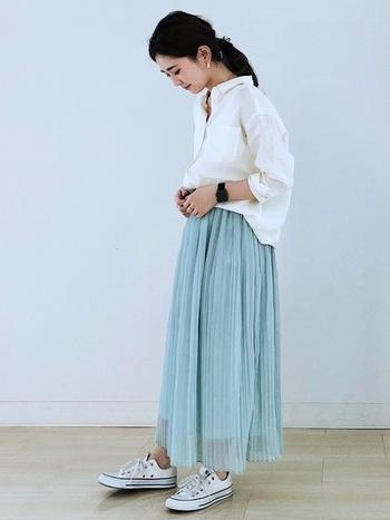 ゆるりと肩のおちたドロップショルダーの白シャツに、ふわりと風に舞うプリーツスカートを合わせたエアリーな着こなし。甘くなり過ぎないように、足元はスニカーで引き締めるのを忘れずに。