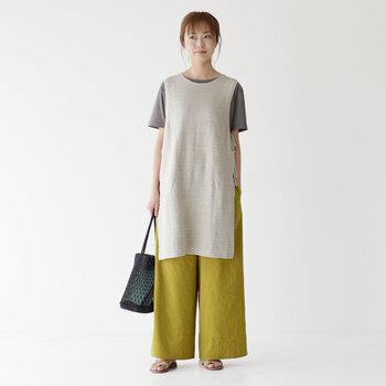 リネンコットン素材のロング丈ベストは、グレーのTシャツとイエロー系のワイドパンツに合わせてナチュラルなテイストに。足元はブラウンのサンダルで涼しげにまとめて、黒のバッグで引き締めカラーを演出しています。
