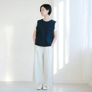 ネイビーのリネン素材ベストに、白Tシャツと白のワイドパンツを合わせた着こなしです。シューズも白で揃えて、統一感のある爽やかなスタイリングに。Tシャツとパンツのカラーを合わせることで、セットアップにニットを重ねているようなおしゃれコーデが楽しめます。
