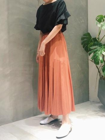 袖のフリルがフェミニンな黒のブラウスは、デニムやシックな色味のボトムスとも好相性。 華やかさを出したいときには、色味のあるフレアースカートで。  とろみのあるオレンジのフレアースカートなら、甘くなりすぎず自然な華やぎ感が。洗練された大人コーデが完成しますよ。
