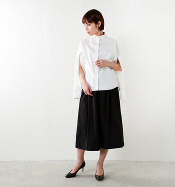 ケープスリーブシャツに黒のスカートを合わせた知的で女性らしいコーデ。Aラインのひざ下丈のスカートにはパンプスを合わせてフェミニンに。シンプルに着こなすことでデザイン性のあるシャツがさらに際立ちます。