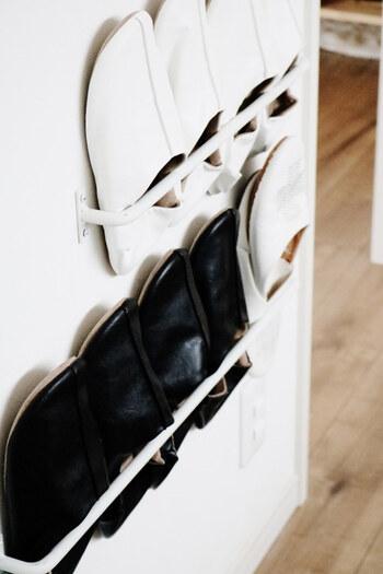 こちらは、壁面を活用したスリッパ収納術です。  アイアンバーを取りつけて、スリッパを差し込む方法で、床に物おかなくて済むので玄関がすっきりした印象に。  壁に設置するもよし、シューズボックスの扉裏に設置するもよし、「見える収納」「隠す収納」のどちらにも使える方法です。  賃貸物件や新築住宅で、壁や扉に穴や傷をつけたくない場合は、剥がれないか確認した上で、「マスキングテープや養生テープ+両面テープ」で設置する方法も。