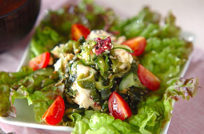 """トマト、キュウリのほかにもレタスや海藻・ゴマが入っていてミネラルもたっぷりの白和えサラダ。家で作る中華風ドレッシングはラー油がピリリと効いて食欲をそそります。甘酢も入っているので唾液の分泌を促進し、夏バテ防止にも◎。焼き肉などメインがお肉料理の副菜にぴったり。<おいしくなるポイント>お好みで豆腐をちいさく崩し""""後和え""""して食べてみて。"""