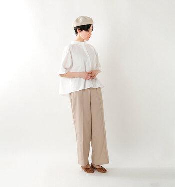 白のスタンドカラーブラウスに、ベージュのワイドパンツを合わせたコーディネートです。きっちりめになりがちなブラウスコーデも、ニュアンスカラーのベレー帽をプラスすることでほっこりやさしい印象に。足元はブラウン系のパンプスで、柔らかなカラーリングに引き締めポイントをプラスしています。