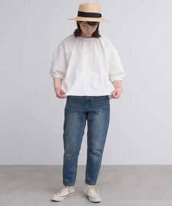さりげなく刺繍の入った白ブラウスに、デニムパンツを合わせたカジュアルなコーディネート。足元はスニーカーでとことんカジュアルにまとめつつ、ナチュラル素材のハットをかぶって涼しげな季節感を演出しています。