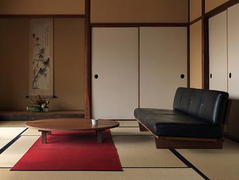 こちらはどっしりとしたローソファーとローテーブルのセットです。床の間のある、和室らしい和室に重厚感のあるソファーがよく似合っています。広い座面が畳のまっすぐなラインをきれいに見せています。深みのある茜色のカーペットがアクセントカラーになっています。