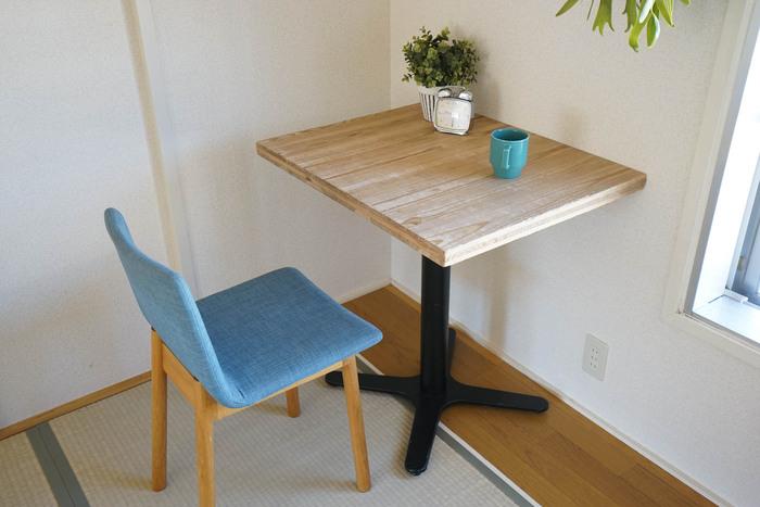 こちらは椅子のファブリックに、深みのあるブルーをチョイス。そのほかに1本脚のカフェテーブル、小さなグリーンなどのナチュラルインテリアとあわせると、あたたかみのある雰囲気に。