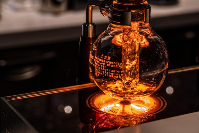 サイフォン式は、蒸気圧の動きを利用したコーヒーの抽出方法です。基本的な構造は、一番下に火元があり、その上にお湯の入ったフラスコ、その上にコーヒー粉を入れるロートがきます。  フラスコ内のお湯が熱せられて蒸気が発生すると、蒸気圧によりフラスコ内のお湯がロートへと移動します。ここでコーヒー粉と撹拌されコーヒーに。火を止めると今度はフラスコ内の気圧が一気に下がり、ロートで作られたコーヒーがフラスコへと移動します。間にあるフィルターによってろ過される仕組みです。
