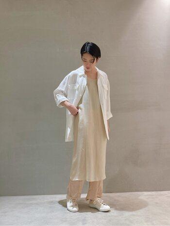 シンプルなベージュカラーのペチワンピースを主役にした着こなし。薄手のシャツやパンツと合わせて、さらりと着心地のいいレイヤードスタイルを。