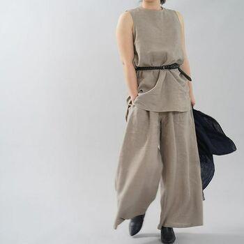 リネン素材のペチタンクなら、さらりと一枚で着ても◎ 同じ素材のパンツと合わせ、ウエストマークでキリリと引き締めた大人の夏コーデ。