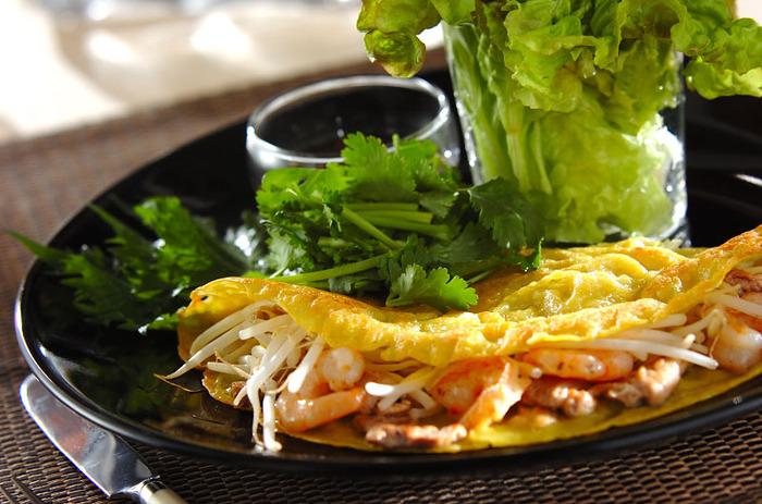 ベトナムの屋台で人気の「バインセオ」。米粉とココナッツミルクのカリッとした皮に肉やモヤシを挟んだ、ベトナム風のお好み焼きです。大葉、ミントの葉、パクチーなどの香菜と一緒に、旨辛のエスニックだれにつけて召し上がれ♪