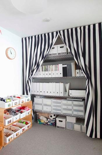 リビング側の壁全面に大型の収納を増やす方法も。 窓を避けるようにして家具をおけば、作り付けのクローゼットのようにも使えますね。  大型の家具を買うのは勇気がいりますが、オープンラック+布で目隠しするアイデアは、気軽にお試しできそうですね。 こちらのお部屋では、アクセントクロスにも見える白黒のストライプの布をかけています。