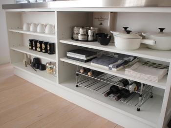 キッチンカウンターがダイニング側に出っ張っている場合は、カウンター下を活用するだけでも収納力が格段にアップします。  こちらのご家庭では、オープンラックにして見える収納にしています。ものはあまり詰め込まずにスッキリと、ディスプレイするような感覚で使っていますね。