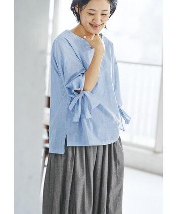袖についたリボンがポイントになった、涼しげなブルーのトップス。白×茶色の細いストライプが、リボンのスイートな雰囲気を大人っぽく引き締めてくれています。