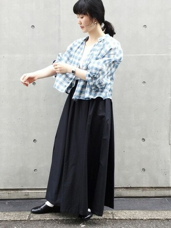 重たい印象を与える黒のスカートも、彩度が低いブルーチェックと合わせれば爽やかさが加わり夏仕様にアップデートが可能です。ウエスト位置の高いロング丈スカート×ショート丈のシャツコンビは、腰の位置が高く見えてスタイルアップ効果も抜群♪暑いときはシャツを肩にかけたり、結んだりしてアレンジするのも◎。