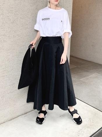 カジュアルなオーバーサイズのロゴTシャツも、ブラックスカートを合わせれば、大人のMIXコーデが楽しめます。Tシャツの袖を無造作にロールアップしてこなれ感を出すと、都会的で洗練された着こなしになります。