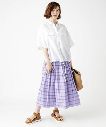 爽やかなパープルのボーダースカートは、風通しが良く涼しいフレアシルエット。ビッグシルエットのシャツを合わせてリラックスした雰囲気に。バッグとサンダルカラーをリンクさせて全体に統一感を。