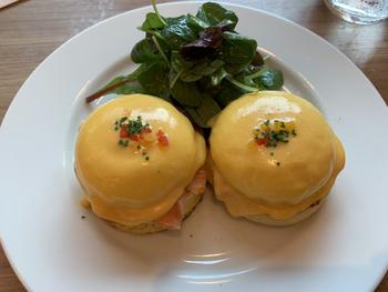 """ランチタイムにいただきたいメニューのひとつが「クラシック エッグベネディクト」。濃厚な自家製オランデーズソースがたっぷりかかった卵とスモークハムの塩気が格別です。ナイフを入れると黄身がとろりと流れ出し、""""ニューヨークの朝食の女王""""と称されるのも納得のひと品。"""