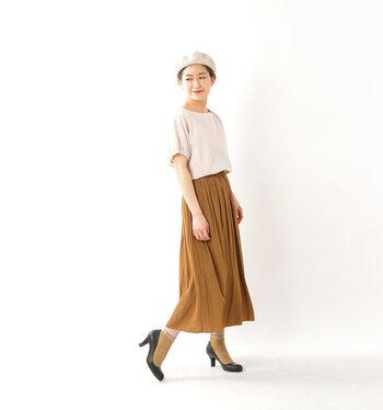 コックリとしたベージュのスカートには、ベージュと黄色を掛け合わせたような同系色のソックスを。パンプスとのバランスを考えるとおしゃれ感UP!トップスはやわらかなカラーを選ぶと、すっきりと上品に仕上がります。