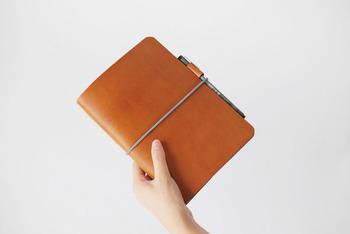 シンプルかつ高級感のある革製の手帳カバー。カバーの中央にあるゴムは手帳を固定するだけでなく、しおりとしても使えますよ。