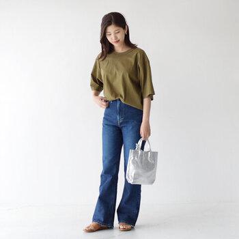 カーキのTシャツと裾がフレアになったデニムを合わせたコーデです。Tシャツはオーバーサイズにすることが、カーキ色でもハンサムになりすぎないポイント。バッグのシルバーの色味が、さりげなくコーデのアクセントに。裾に向けてさりげなく広がったデニムのデザインがスタイルアップを叶えます。