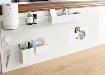 キッチンカウンター周りのちょっとしたスペースに壁面収納をつくっています。白で統一されているので、生活感の出やすい雑貨も洗練された印象に。小物入れをマグネットで設置できるので気分に合わせて変えやすいのも魅力。モノが出し入れしやすく、見た目も素敵な工夫です。