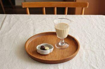 ほんのひと口のお菓子でも、きちんとお皿を用意して丸盆にのせてあげると、ティータイムが盛り上がります。  こちらの丸盆は木目をまっすぐに縦のラインを強調して、グラスの縦長シルエットとリンク。おしゃれなカフェタイムになります。
