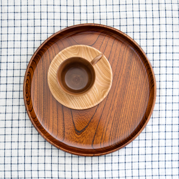 こちらのお盆は、神奈川県、小田原の伝統工芸品で仁取盆(にとりぼん)とよばれるものです。けやきに漆塗装を施し、漆らしい端正な艶めきを与えています。漆塗りのお盆は、強度もあり熱にも強いという特徴があります。ほどよい重みが手にかかり、安定しています。