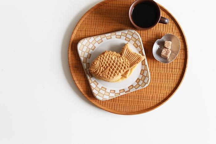 木工作家の高塚和則さんが作り出す趣深い丸盆は、均等に並んだ彫り模様が優雅な印象です。素朴なたい焼きがとても美味しそうに見えます。彫り模様を横向きにするか、縦向きにするかでイメージが変わります。