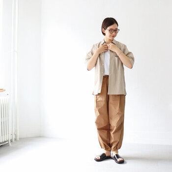 キャメルカラーのワイドパンツに、白トップスとベージュのシャツを合わせたボーイッシュなスタイリング。足元は黒のサンダルで、全体をキュッと引き締めるワンポイントに活用しています。