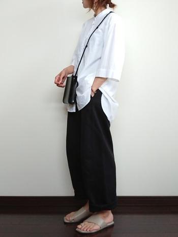 ユニクロの黒ワイドパンツに、白シャツを合わせたモノトーンコーディネート。バッグは黒でパンツと色を揃えつつ、足元はベージュのサンダルで夏らしい着こなしに仕上げています。