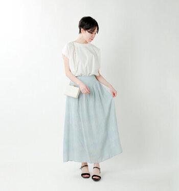 淡いサックスブルーのロングスカートに、ふんわりシルエットの白トップスを合わせた爽やかなコーディネートです。足元は黒のサンダルで、引き締めカラーをさりげなくプラス。バッグは白のショルダーをチョイスして、全体的に上品な印象でまとめています。