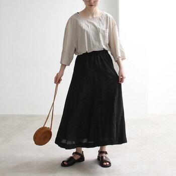 黒のロングスカートに、ベージュのトップスをタックインしたスタイリング。足元はボリューム感のあるサンダルで、ナチュラルなアイテム同士の組み合わせにアクセントをプラスしています。ブラウンの小さめショルダーは、丸形でトレンド感も◎