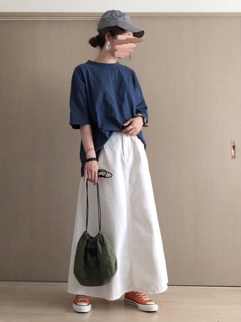 「GU(ジーユー)」の白ロングスカートは、デニム生地をチョイスしてカジュアルなコーディネートに。ネイビーのトップスをフロントだけちょこんとタックインして、リラックス感が出過ぎないようワンポイントをプラスしています。デニム生地に合わせて、キャップやスニーカーでスポーティーな印象に。