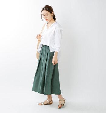 グリーンのロングスカートに、白のブラウスをフロントだけタックインしたコーディネートです。袖丈が長めのトップスですが、ロールアップと深めのVネックで、暑苦しい印象にならないよう着こなしています。ロングスカート×白ブラウスのキレイめコーデを、フラットなサンダルで上手にカジュアルダウンしているのもポイントです。