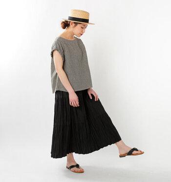 ギンガムチェックのトップスに、黒のロングスカートを合わせたモノトーンコーデ。サンダルも黒で揃えつつ、ナチュラル素材のハットを取り入れることで重たくなりすぎないようまとめています。袖丈の短いトップスを選んでいるので、黒スカートも軽やかな印象に。