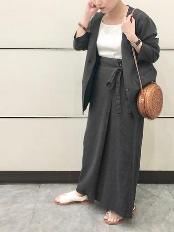 ダークトーンのグレーロングスカートに、同色のノーカラージャケットを合わせたセットアップ風コーデ。インナーはシンプルな白をチョイスして、サンダルもカラーを合わせているのがポイントです。ラウンドショルダーを大きめのトートバッグなどに変えれば、夏のオフィスカジュアルにも活躍してくれそうな着こなしですね。