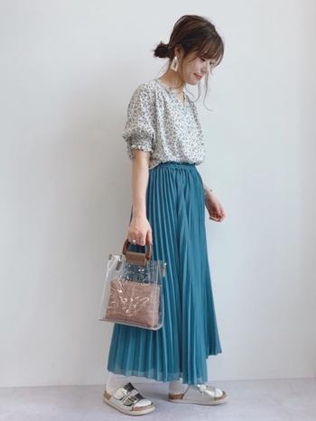 ブルーグリーンのロングスカートに、花柄ブラウスをふんわりとタックインしたスタイリングです。中が見えるクリアバッグは、涼しげで暑い夏の日にもぴったり。足元はサンダル×靴下のレイヤードスタイルで、フェミニンな着こなしに程よい抜け感をプラスしています。