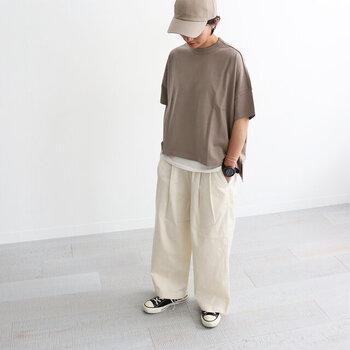 クリームカラーの白系ワイドパンツに、ブラウンの無地Tシャツを合わせたシンプルなボーイッシュコーデ。スニーカーとキャップを合わせて、ゆるアイテムをカジュアルにまとめています。トップスから白のインナーをチラ見せした、レイヤードスタイルは今っぽさ抜群の着こなしです。