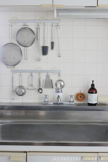 人気ブログ「シンプルライフ × シンプルスタイル」のDAHLIAさんのキッチンです。白いタイルの壁面と、シンクのシルバー。この備え付けの色みを基調として、シルバーのキッチンツールで統一されています。  タワシとハンドソープのブラウンカラーがきれいなアクセントに。まさにシンプルライフを志すキッチンのお手本ですね。