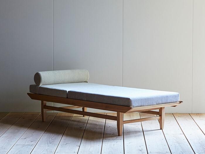 長崎の家具メーカー「AJIM」のデイベッドは、モダンながらもぬくもりのあるデザイン。ちょこんと乗った丸いクッションがかわいらしく寝心地も◎ フレームの上にクッションが乗せられた様は、まるで川に浮かぶ笹舟のようです。
