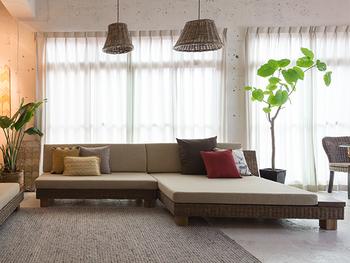 こちらはデイベッドのような広々としたソファが置かれた、リラックス&リゾート感溢れるインテリアコーディネートです。黄色や赤色のファブリック、植物のグリーンが差し色となり、お部屋の良いポイントになっています。座面が低いソファを置くことで天井が高く見え、開放的な空間が広がります。