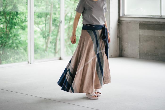 布を贅沢にたっぷり使ったロングの巻きスカートは、一つ一つ柄が微妙に違う一点もの。染めから織り、縫製までこだわった製品は、すべて自社で生産されています。