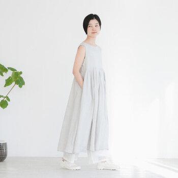 薄いグレーのノースリーブワンピースは、ふわっと広がるフレアシルエットが特徴。ロング丈のデザインなので、あえて足元から少しだけワイドパンツを見せてこなれ感たっぷりな着こなしにまとめています。シューズも白で揃えて、全体をナチュラルな雰囲気に。
