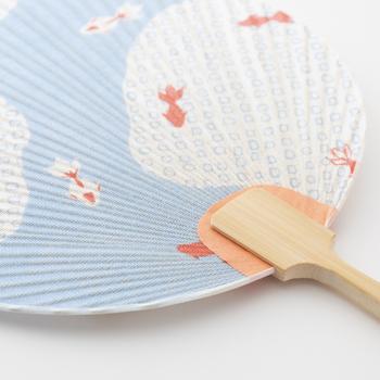 奈良の工芸「かや織」で作られたうちわです。蚊帳に使われる目の粗い織物で、紙とは違った質感を楽しめます。金魚が水面を泳いでいるデザインも涼しげで素敵♪