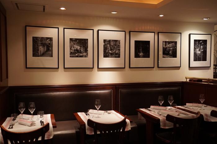 毘沙門天からほど近い路地にある「LUGDUNUM Bouchon Lyonnais(ルグドゥノム・ブション・リヨネ)」は、南フランスのリヨンで生まれたオーナーシェフ・クリストフ ポコ氏が手がけるレストラン。  店内に入ると、リヨンの風景写真やポスターや重厚な樫の木のテーブルが目を惹きます。2階に続く螺旋階段は1900年代に作られたものだそう。